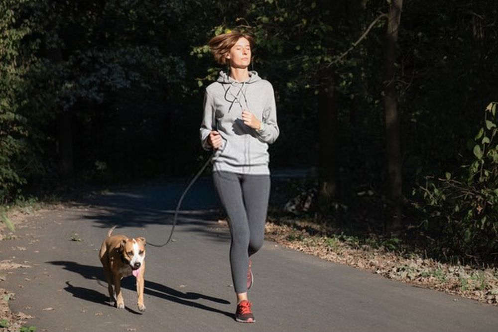 Woman jogging with dog in a park